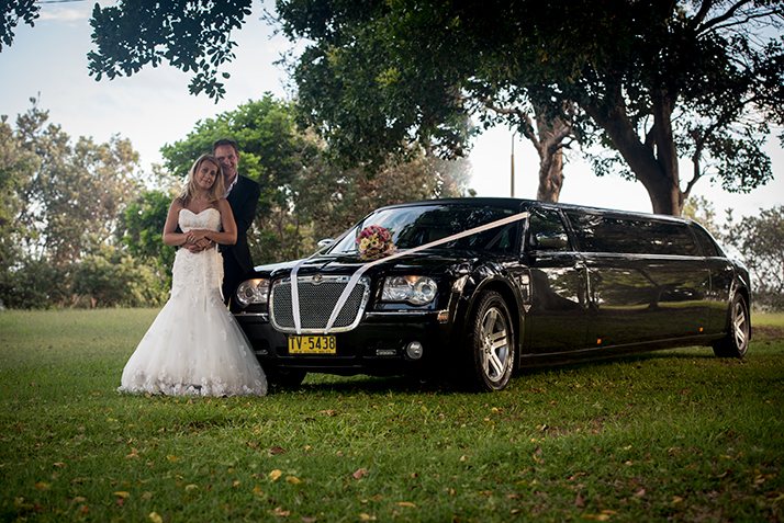 Bride and groom with limousine