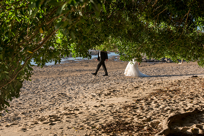 Bride following groom on the beach masked by foliage